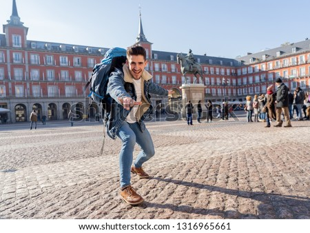 Happy young man traveling around Europe having fun pretending to surf in Plaza de Espa–a, Madrid, Spain. In People Vacations, adventure, backpacking, student lifestyle and surfing the world concept. Foto stock ©