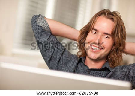 Happy Young Man Using A Laptop Computer with Hands Behind His Head.