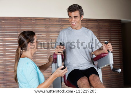 Happy young man using an exercise machine while looking at instructor in health club