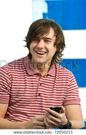 Happy young man using mobile phone, looking at camera
