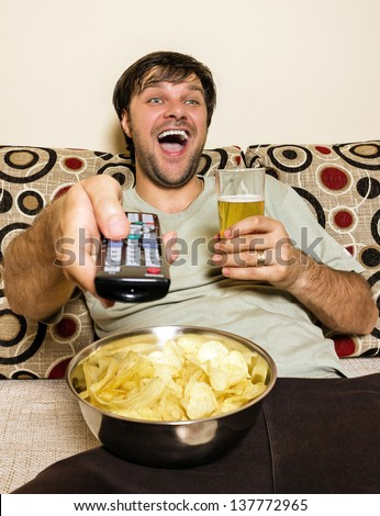 Happy young man watching television, eating potato chips and drinking beer inside
