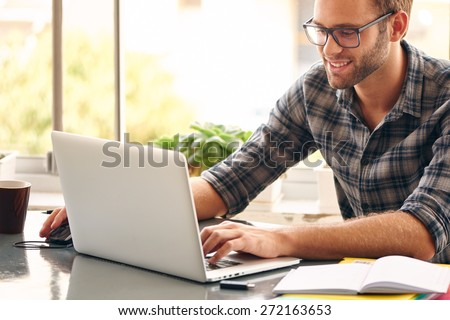 Happy young man, wearing glasses and smiling, as he works on his laptop to get all his business done early in the morning with his cup of coffee