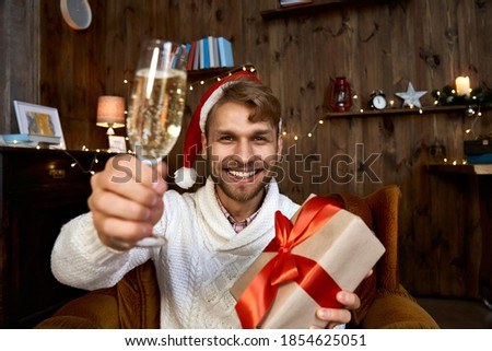 Happy young man wearing santa hat holding Christmas gift looking at camera. Excited guy drinking champagne having virtual chat with friend celebrating New Year distance online party. Web cam view