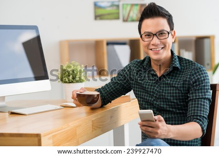 Happy young man with a cellphone looking at the camera