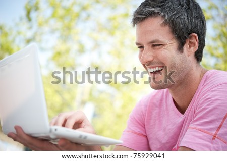 Happy young man with a laptop outdoors