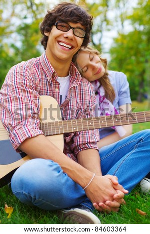 Happy young man with acoustic guitar and his romantic girlfriend in park outdoor