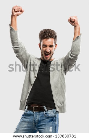 Happy young man with arms up, over a gray background