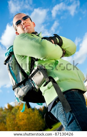 Happy young man with backpack in the park.