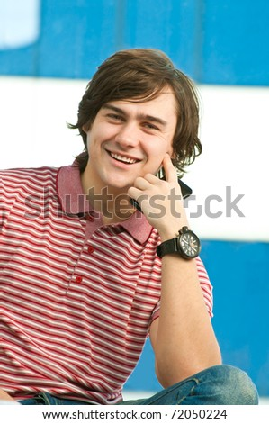 Happy young man with mobile phone, looking at camera