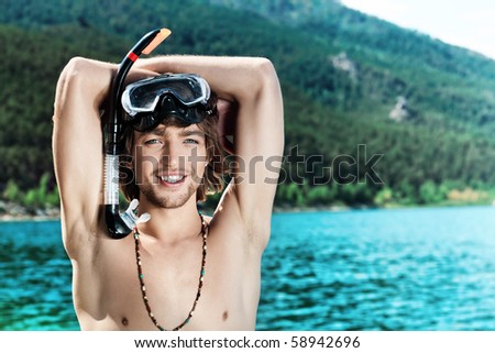 Happy young man with snorkelling gear standing on a sea beach.