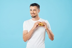 Happy young man with wolf hamburger on a blue background cropped view