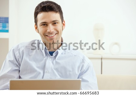 Happy young man working on laptop computer, smiling.?