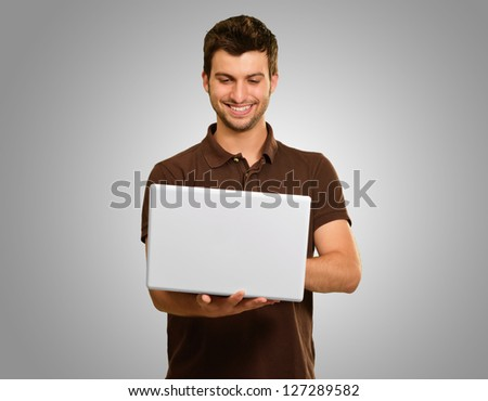 Happy Young Man Working On Laptop On Grey Background