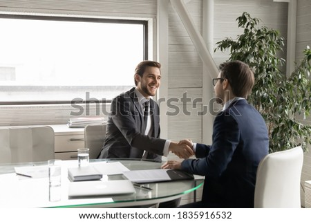 Happy young manager shaking hands with leader, feeling thankful for new job offer. Satisfied with good working results ceo executive manager praising male employee at meeting, sitting at table. Foto stock ©