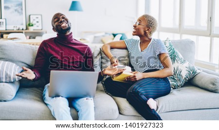 Happy young marriage having conversation on laughing while spending time on hobby during weekend with book and laptop computer, cheerful african american couple in love having fun together
