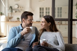 Happy young married couple enjoying cozy romantic weekend time with cup of hot tea coffee chocolate. Smiling pleasant family spouse relaxing on sofa, heart-to-hear talk, spending evening together.