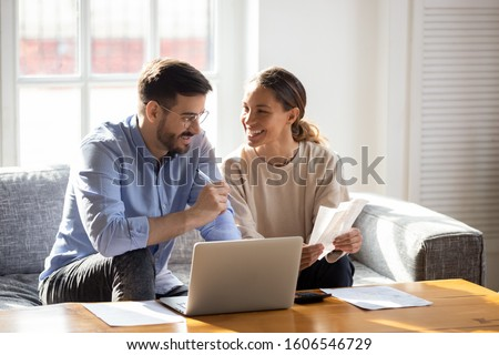 Photo of  Happy young married couple sit on couch calculate expenses use easy online banking service at home, smiling millennial husband and wife count taxes house expenditures pay bills on internet