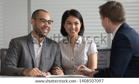 Happy young mixed ethnicity family couple customers listening to bank manager broker insurer consulting clients explaining mortgage investment insurance real estate deal benefits at business meeting