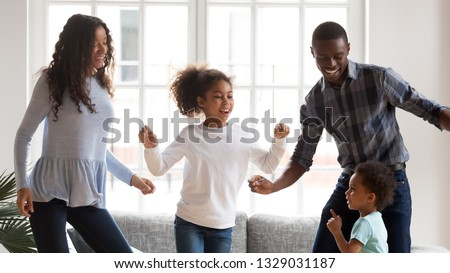 Happy young mixed race family of four have fun together in living room, African American mom and dad entertain with little kids, dancing at home, black parents enjoy spending time with small children