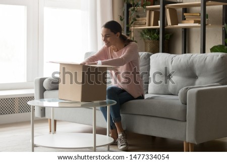 Happy young mixed race woman sitting on couch at home, unpacking huge long awaited cardboard box or parcel, delivery from popular international online store, satisfied with provided postal service.