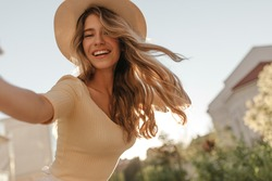 Happy young model makes photo holding camera in hand close-up. Her hair is flying in wind, she is wearing hat. Outdoor photo.