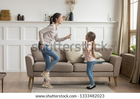 Happy young mom baby sitter sister and cute funny little kid daughter laughing dancing in living room together, cheerful active mother with child girl having fun enjoy moving to music playing at home