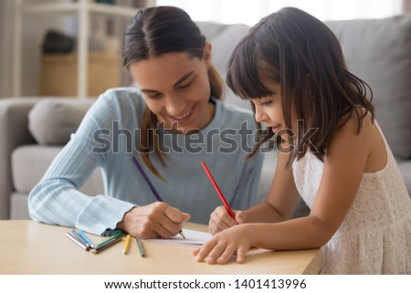 Happy young mom have fun drawing using colorful pencils with cute little daughter, smiling preschooler girl enjoy spend time painting picture with nanny, parent and kid entertain engaged in activity