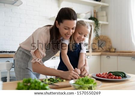 Happy young mom teaching preschool daughter holding knife cut fresh vegetables in kitchen interior, cute little child girl learning cooking prepare salad healthy food with mum enjoy family lifestyle