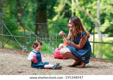 Happy young mother and adorable toddler girl blowing soap bubbles and having fun together, outdoors.