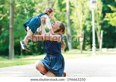 Happy young mother and adorable toddler girl walking through summer park and having fun together, outdoors.