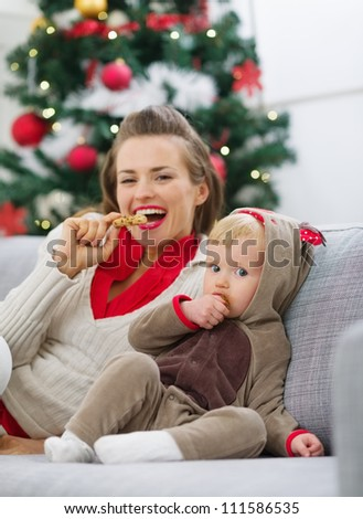 Happy young mother and baby eating cookies near Christmas tree