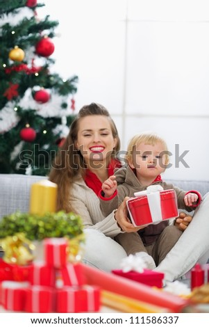 Happy young mother and baby looking on table with Christmas gifts