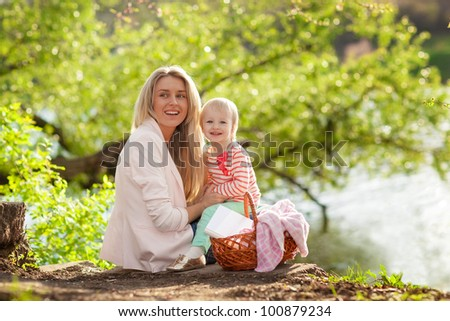 Happy young mother and child having rest near the river