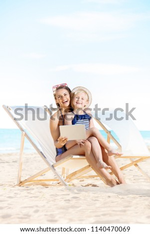 happy young mother and child in swimsuit on the seashore using tablet PC while sitting on beach chairs Foto stock ©