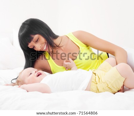 happy young mother and her baby on the bed at home