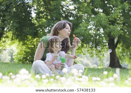 Happy young mother and her daughter blowing soap bubbles in park