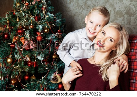 happy young mother and her son at home with a Christmas tree