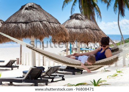 Happy young mother and her son in a hammock on a Caribbean beach