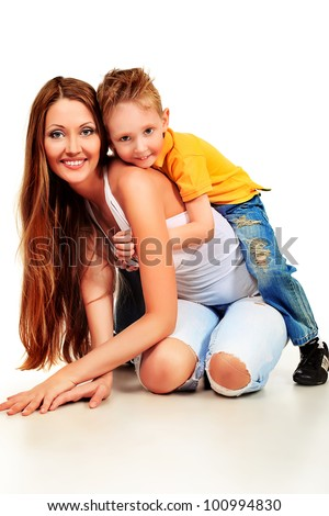 Happy young mother and her son posing together. Isolated over white.