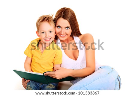 Happy young mother and her son reading a book together. Isolated over white.
