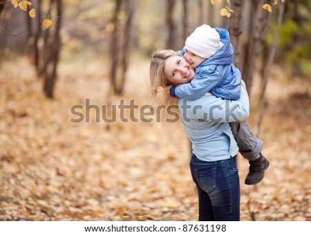 happy young mother and her son spending time in the autumn park (focus on the woman)