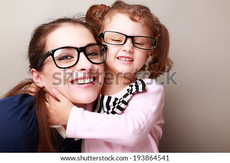Happy young mother and laughing kid in fashion glasses hugging
