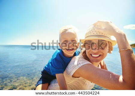 Happy young mother and son on a tropical beach with the laughing little boy getting a piggy back ride on her back