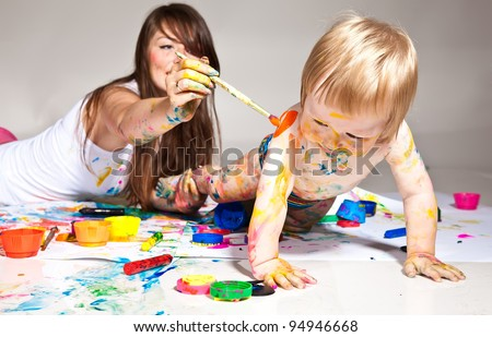 happy young mother and son painting - stock photo