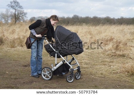 Happy young Mother caring for her baby in a pushchair in Richmond Park, London