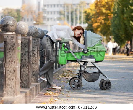 Happy young mother carrying baby in autumn park
