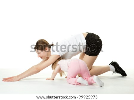 Happy young mother doing sport exercises with her little daughter; white background