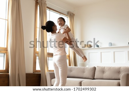 Happy young mother have fun with little preschooler sweet daughter people play together at home. Active overjoyed asian mom holds lifts kid girl sway her enjoy family weekend in living room concept
