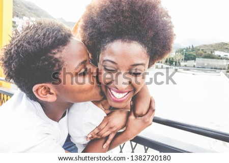 Happy young mother having fun with her child in summer day - Son kissing his mum outdoor - Family lifestyle, motherhood, love and tender moments concept - Focus on woman face #1382720180