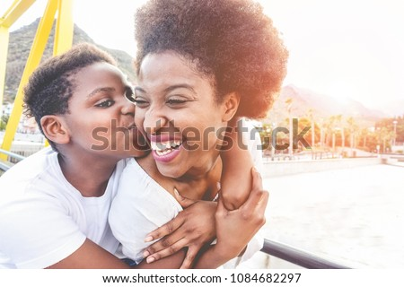Happy young mother having fun with her child in summer sunny day - Son kissing his mum outdoor with back sun light - Family lifestyle, motherhood, love and tender moments concept - Focus on woman face #1084682297